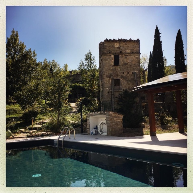 The solar panels are mounted on a pergola next to the swimming pool Tesla Solar Umbria